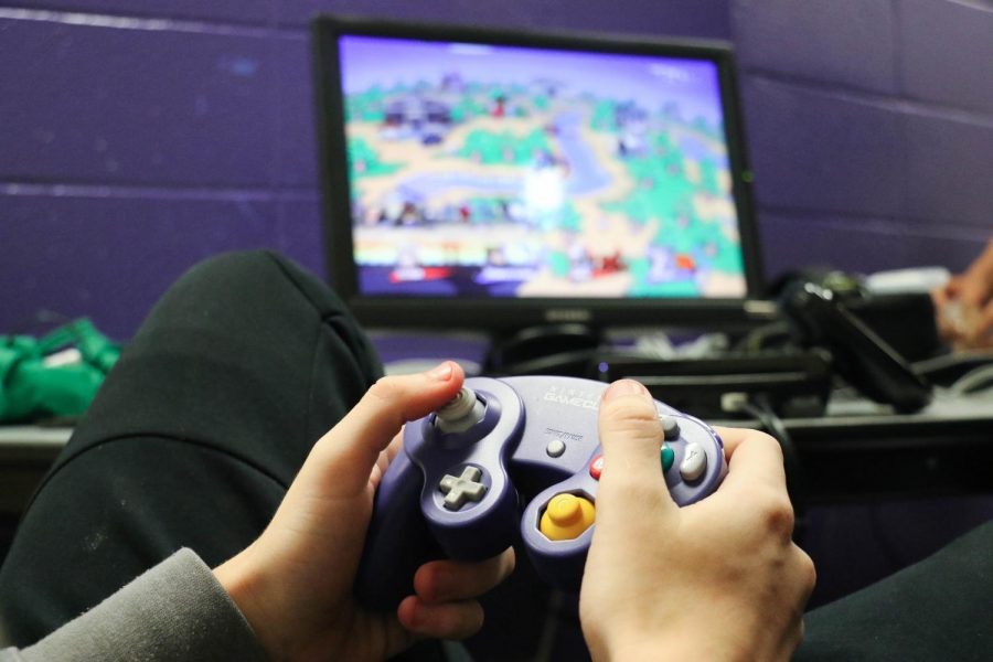 Members of Super Smash Compadres settle down with their controllers to play Super Smash Bros. photo by Jorge Villa